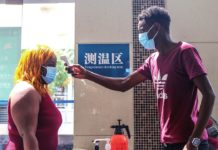 Barry (right), a college student at Central China Normal University from Gambia, checks a female student's body temperature on August 28, serving as an anti-epidemic volunteer. Photo: Courtesy of CCNU