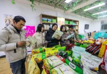Customers buy poverty relief products, such as lotus, mushrooms and rice noodle processed by local enterprises at a store in Guangchang county, Fuzhou, east China's Jiangxi province, Dec. 10. (Photo by Zeng Henggui/People's Daily Online)