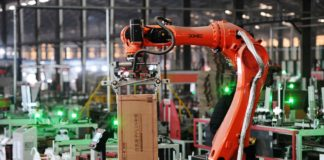 A robotic arm picks up a package of products on the automatic intelligent production line of Xinjingxiang Ceramics Co., Ltd. in Gao'an city, east China's Jiangxi province, Dec. 10. (Photo by Zhou Liang/People's Daily Online)