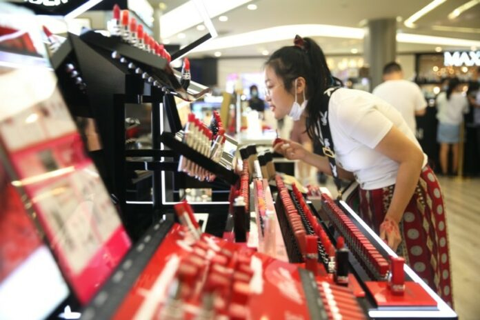 A young consumer selects cosmetics at a duty-free store in Sanya, south China's Hainan province, July 29, 2020. (Photo by Zhang Jingang/People's Daily Online)