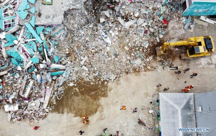 Aerial photo shows an excavator working on damaged buildings during a search operation after a 6.2-magnitude earthquake in Mamuju, West Sulawesi, Indonesia, Jan. 17, 2021. The death toll of a 6.2-magnitude earthquake that struck Indonesia's West Sulawesi province has risen to 73 with over 27,000 people taking shelters, the National Disaster Management Agency said on Sunday. (Photo by Niaz Syarief/Xinhua)