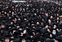 Thousands of ultra-Orthodox Jews attend a funeral procession for Rabbi Meshulam Dovid Soloveitchik in Jerusalem on January 31, defying lockdown rules MENAHEM KAHANA AFP