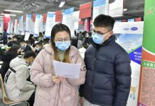 Two college graduates talk at a career fair on campus in east China's Shandong province, Qingdao on Jan. 4. Photo by Han Hongshuo/People's Daily Online