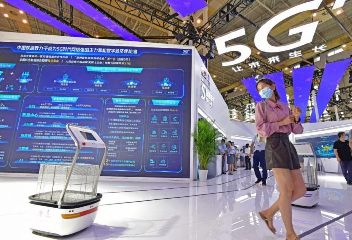 A visitor tries a self-driving shopping cart at an exhibition of the World Digital Economy Conference in Ningbo, east China's Zhejiang province, Sept. 11, 2020. (Photo by Zhang Yongtao/People's Daily Online)