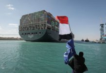 "Cargo ship stuck in Suez Canal freed A worker waves the Egyptian flag as the ""Ever Given"" container ship operated by the Evergreen Marine Corporation, sails with tugboats through the Suez Canal, after it was fully freed and floated. Egypt's Suez Canal Authority announced that the stranded massive container ship that has blocked the Suez Canal for nearly a week, has been fully dislodged and successfully floating in the canal. (best quality available) Photo: -/Suez Canal Authority/dpa"