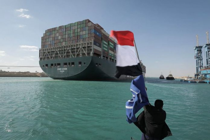 Cargo ship stuck in Suez Canal freed A worker waves the Egyptian flag as the