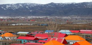Photo taken on March 26 shows a picturesque view formed by colorful residential buildings and snow-covered mountains in Burqin County, Altay, northwest China's Xinjiang Uygur Autonomous Region. (Photo by Wang Jianfeng/People's Daily Online)