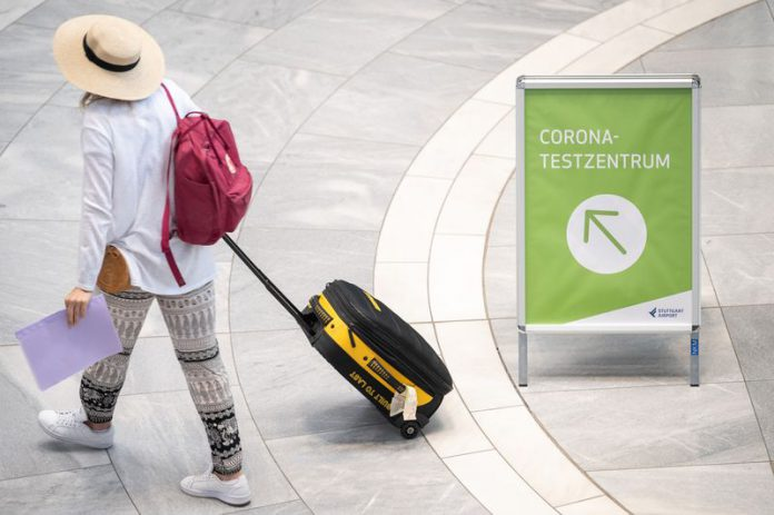 FILED - A traveler walks past a sign for a coronavirus testing centre in Stuttgart's airport in August. A new requirement for people arriving at German airports to have submitted to coronavirus testing has been postponed from Sunday to Tuesday, Health Minister Jens Spahn said on Friday. Photo: Sebastian Gollnow/dpa