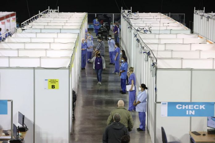 Health workers line up in front of booths at the newly opened Covid-19 vaccination centre in the SSE Arena of Belfast. Photo: Liam Mcburney/PA Wire/dpa