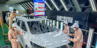 Workers polish a vehicle before adding the finishing coat at a manufacturing base of FAW Haima Automobile Co., Ltd. in Haikou, south China's Hainan province, March 1, 2021. (Photo by Yuan Chen/People's Daily Online)