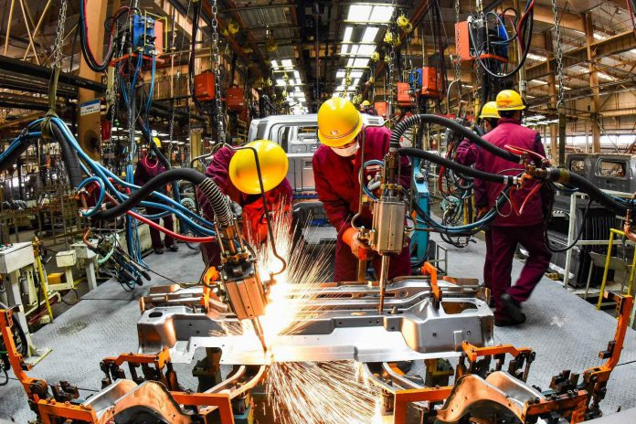 Employees work in a welding workshop of an automaker in Qingzhou, east China's Shandong Province, Feb. 28, 2021. (Photo by Wang Jilin/People's Daily Online)