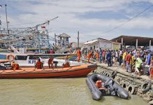 Residents look on as members of National Search and Rescue Agency (BASARNAS) prepare for a search mission for the victims of a ship collision, at a port in Indramayu, West java, Indonesia, Sunday, April 4, 2021. The collision between a cargo ship and a fishing boat left a number of people missing off Indonesia's main island of Java, officials said Sunday. - AP