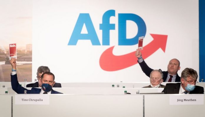 Tino Chrupalla (l), AfD national spokesman, raises his voting card next to Alexander Gauland (2nd from right), AfD parliamentary party leader, and Jörg Meuthen (r), AfD national spokesman, in the Dresden exhibition hall at the AfD national party conference. One topic is the resolution of the election program for the Bundestag elections. Photo: Kay Nietfeld/dpa