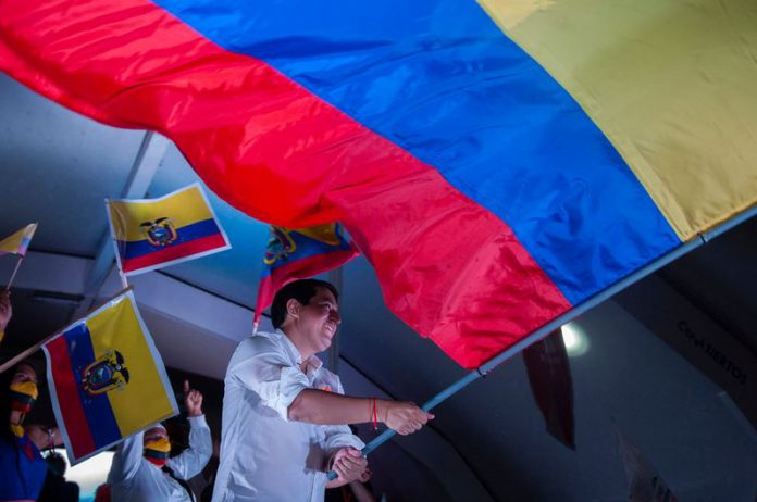 Andres Arauz, presidential candidate in Ecuador, waves a large national flag on stage at the end of his campaign on Thursday. He is tied at about 50 per cent in the race against conservative banker Guillermo Lasso. Photo: Juan Diego Montenegro/dpa