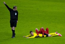 FILED - Bayern Munich's Leon Goretzka (above) and Borussia Dortmund's Thorgan Hazard on the ground next to referee Marco Fritz during a Bundesliga game. Both clubs have been invited to join the breakway European Super League despite voicing opposition, the Spiegel magazine has reported. Photo: Günther Schiffmann/AFP-POOL/dpa
