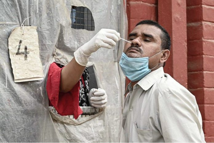 A health worker collects a swab sample from a man for Coronavirus (Covid-19) PCR test. Photo: Prabhat Kumar Verma/ZUMA Wire/dpa