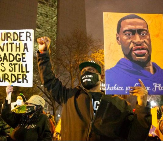 FILED - A demonstrator holds a portrait of George Floyd while raising his fist during a march against police brutality amid Derek Chauvin's trial in the downtown of Minneapolis. Photo: Henry Pan/ZUMA Wire/dpa
