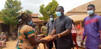John Kumah giving cloth to widows.