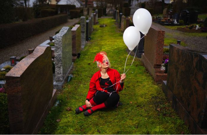 FILED - The clown Kaala Knuffl holds balloons in a cemetery in Germany. She's not out of place here - Kaala Knuffl offers graveside services. Photo: Nicolas Armer/dpa
