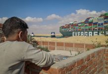 "FILED - A boy observes two tugboats taking part in the refloating operation carried out to free the ""Ever Given"" container ship while it was stuck in the Suez Canal last month. The Suez Canal is ready to accept an out-of-court settlement with a massive container ship that blocked the vital waterway for almost a week last month, an Egyptian official has said. Photo: Samuel Mohsen/dpa"