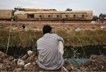 18 April 2021, Egypt, Sandahur: A man inspects the damaged wagons of a passenger train that derailed at the village of Sandahur near Banha in Qalyubia Governorate. Eight carriages of the train derailed injuring at least 109 people, according to figures released by local authorities. Photo: Sayed Hassan/dpa