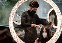 A hairdresser brushes a woman's hair at Aldo Coppola Rinascente hair salon, as from today in Milan, shops and hair salons are reopened after easing the coronavirus restrictions. Photo: Claudio Furlan/LaPresse via ZUMA Press/dpa