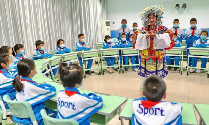 Photo taken on March 26 shows an activity held in a primary school in Qinhuangdao, north China's Hebei province to promote traditional Chinese operas among students. (Photo by Cao Jianxiong/People' s Daily Online)