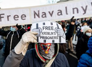 """Ademonstrator holds a sign reading """"Free Kremlin's Prisoners"""" during a demonstration on January 31, 2021, against the detention of Russian opposition leader Alexei Navalny. Photo: Fabian Sommer/dpa"""