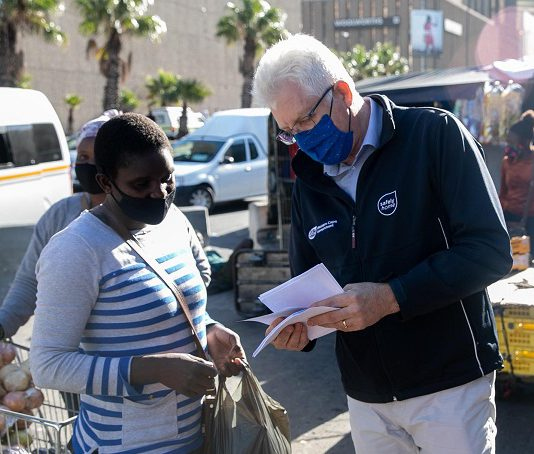 Alan Winde (R), premier of South Africa's Western Cape Province, talks with a woman during a vaccination registration drive outside a railway station in Cape Town, South Africa, on May 11, 2021. Alan Winde said in an interview with Xinhua on Tuesday that the third COVID-19 wave will occur in the province in the next few weeks, while reaffirming that foreign residents can register for vaccines. (Xinhua/Lyu Tianran)