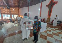 Rev Fr Dominic Apee, the Visiting Priest who presided over the Mass presenting the citation to Mr James Nsoh, the Patron on St Dominic Savio Mass Servers Association