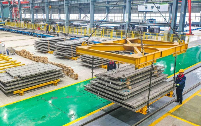 Workers of Zhejiang Dadongwu Group Co., Ltd., a comprehensive enterprise that provides green building materials, produce components for green buildings at the company's integrated green building industrial base in Huzhou city, east China's Zhejiang province, Feb. 28, 2021. (Photo by Fu Lijia/People's Daily Online)