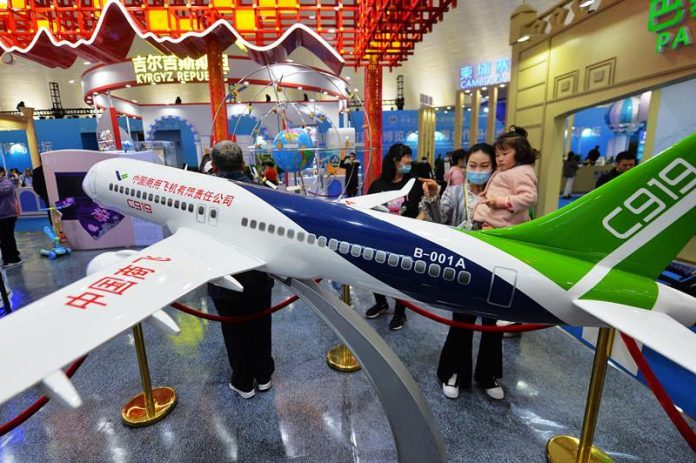 Visitors watch the model of Chinese-made aircraft C919 at the 2021 Shanghai Cooperation Organization International Investment and Trade Expo held in Qingdao, east China's Shandong province, April 28, 2021. (Photo by Wang Haibin/People's Daily Online)