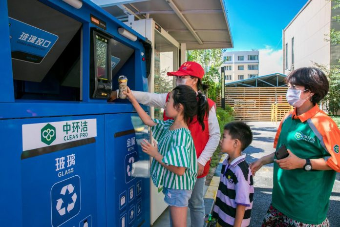Community volunteers show children how to use a smart waste sorting and recycling facility in a residential community in Yuquan district, Hohhot city, capital of north China's Inner Mongolia autonomous region, Aug. 4, 2020. (Photo by Ding Genhou/People's Daily Online)