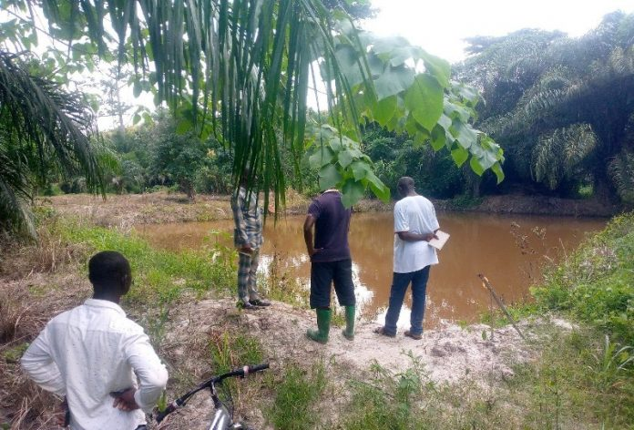 some of the fish farmers standing beside one of the fish ponds