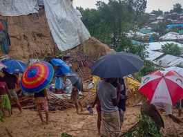 Onlookers stand as Rohingya refugees work amid the debris of houses in Balukhali camp that were damaged after heavy downpour [Tanbir Miraj/AFP]