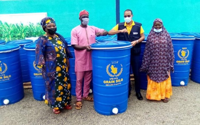 Mr Nikoi (in yellow shirt) presenting the silos to some of the beneficiaries