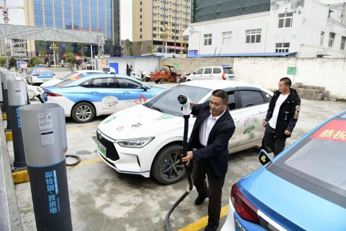 A taxi driver charges his pure electric vehicle at a charging station in Anlong county, southwest China's Guizhou province, March 10, 2021. (Photo by Liu Zhaofu/People's Daily Online)