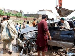 People examine a damaged vehicle after heavy rains in Islamabad, capital of Pakistan, on July 28, 2021. Pakistani officials said on Wednesday that heavy rains have wreaked havoc in the country's federal capital Islamabad, killing at least two people while injuring several others. (Xinhua/Ahmad Kamal)