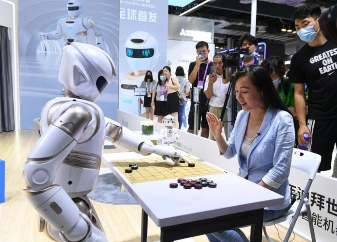 A visitor plays Chinese chess with a humanoid robot during the warm-up for the 2021 World Artificial Intelligence Conference (WAIC) held in east China's Shanghai, July 7, 2021. (Photo by Yang Jianzheng/People's Daily Online)