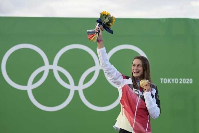 Ricarda Funk of Germany holds the gold medal after winning in the Women's K1 of the Canoe Slalom at the 2020 Summer Olympics, Tuesday, July 27, 2021, in Tokyo, Japan. (AP Photo/Kirsty Wigglesworth)