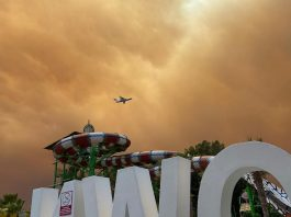 28 July 2021, Turkey, Side: Smoke drifts over leisure facilities at a hotel complex in the Turkish resort region of Antalya as a plane is on approach to land. Winds drove flames from several wildfires toward residential districts, the district administrator of Manavgat told CNN Turk. Photo: Cevin Dettlaff/dpa-Zentralbild/dpa
