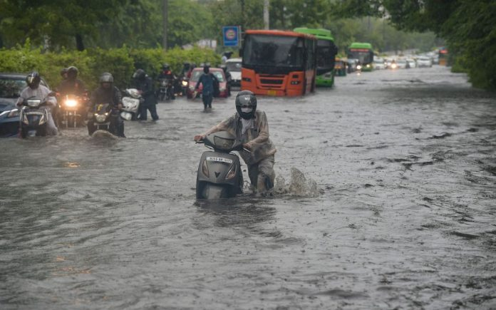 A commuter pushes his scooter across a flooded road on July 19, after heavy monsoon rains. More than 100 people are dead and scores are missing after landslides, floods, house collapses and other incidents brought on by monsoon rains in western India, officials said on Sunday. Photo: Manvender Vashist/PTI/dpa