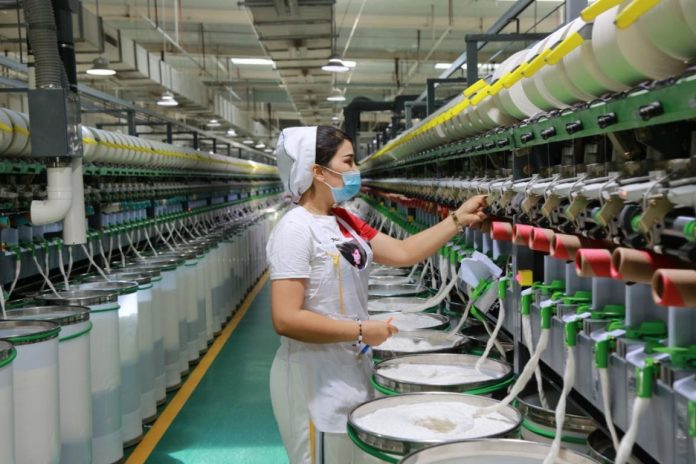 A woman works at a workshop of a textile factory in Awat county, Aksu, northwest China's Xinjiang Uygur autonomous region, July 10, 2021. The factory is preparing a 1,200-tonne order for its clients in Shandong, Jiangsu and Zhejiang provinces. (Photo by Bao Liangting/People's Daily Online)
