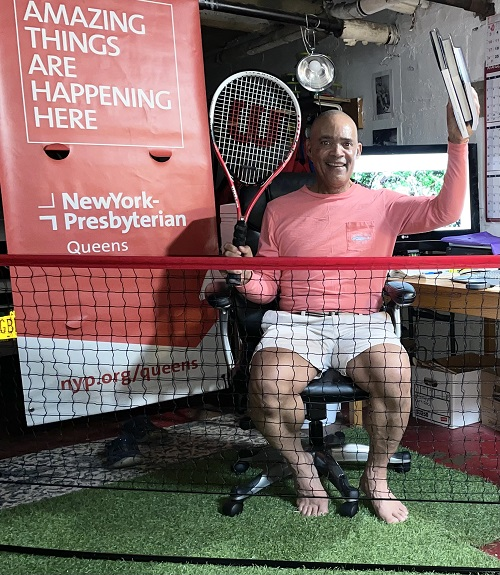 Don Victor Mooney in his garage. Mooney holds a tennis racket and books with a New York Presbyterian - Queens banner he found abandoned during his walks at Flushing Meadow Park. He has contacted the hospital, with the hope it can hang once again. Mooney was admitted two times to the hospital, most recently in June. (GC MEDIA - August 17, 2021)