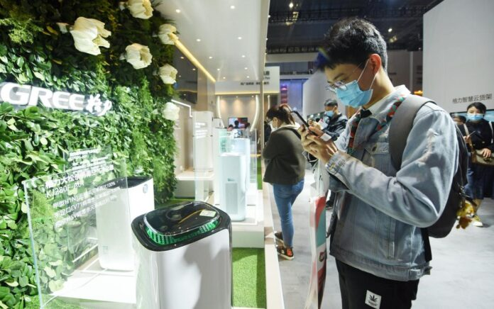 A visitor watches an air purifier launched by Gree Electric Appliances Inc., China's leading home appliance manufacturer, at the Appliance & Electronics World Expo 2021 (AWE) held in east China's Shanghai, March 23, 2021. (Photo by Long Wei/People's Daily Online)
