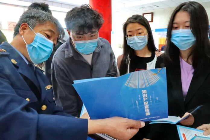 A staff member of the intellectual property (IP) administration of Haigang district, Qinhuangdao city, north China's Hebei province, promotes knowledge about IP among college students, April 25, 2021. (Photo by Cao Jianxiong/People's Daily Online)