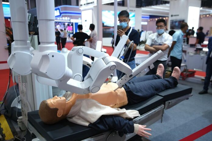 A 5G-enabled surgical robot is displayed at the 2021 World Robot Conference held in Beijing, Sept. 12, 2021. (Photo by Guo Junfeng/People's Daily Online)